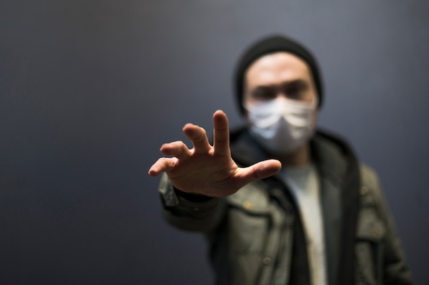 Vorderansicht des defokussierten mannes mit der medizinischen maske, die nach jemandem greift