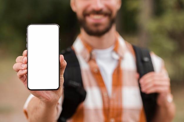 Vorderansicht des defokussierten mannes mit rucksack, der smartphone hält