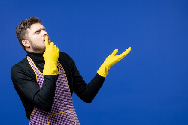 Vorderansicht des denkenden jungen mannes, der den zeigefinger auf den mund legt, der auf der blauen wand steht