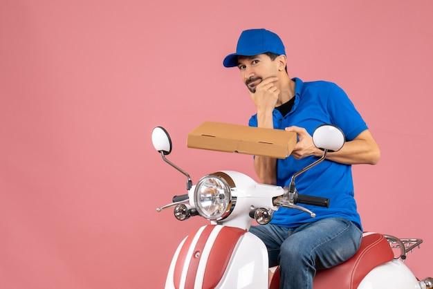 Vorderansicht des denkenden kuriermannes mit hut, der auf dem roller sitzt und die bestellung auf pastellfarbenem pfirsichhintergrund hält