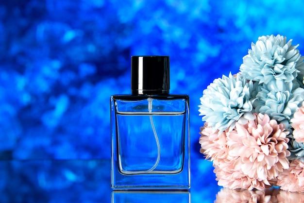 Vorderansicht des eleganten frauenparfüms und der farbigen blumen auf blauem hintergrund