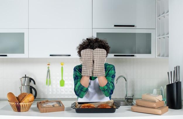 Vorderansicht des emotionalen kerls, der einen halter trägt, der sein gesicht bedeckt, der hinter dem tisch mit frisch gebackenem gebäck darauf in der weißen küche steht