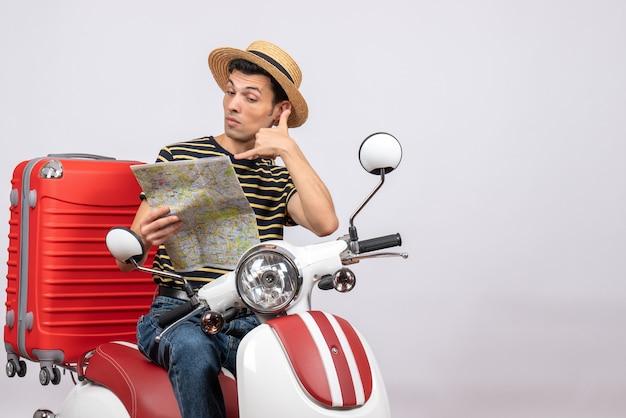 Vorderansicht des entschlossenen jungen mannes mit strohhut auf moped-rufzeichen