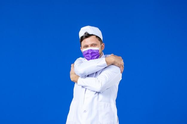 Vorderansicht des entzückten männlichen arztes im medizinischen anzug und in der lila maske auf blauer wand