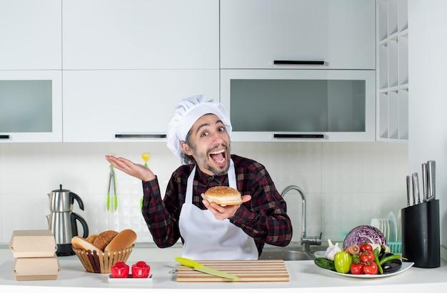 Vorderansicht des erfreuten männlichen kochs, der brot hält