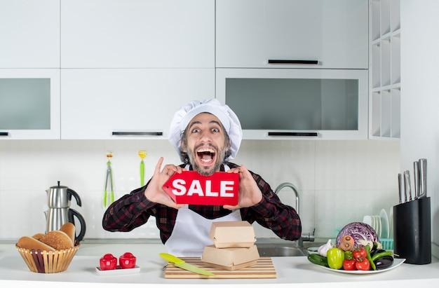 Vorderansicht des erfreuten männlichen kochs, der das verkaufsschild in der küche hält