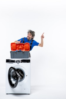Vorderansicht des erfreuten mechanikers, der auf die weiße wand rechts hinter der waschmaschine zeigt