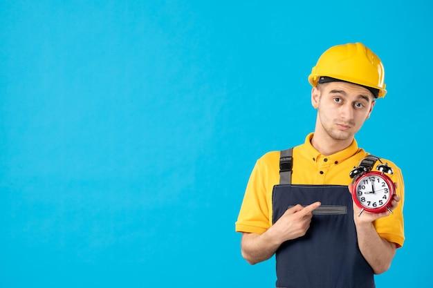 Vorderansicht des ernsthaften männlichen arbeiters in der gelben uniform mit uhren auf blau