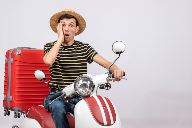 Vorderansicht des erstaunten jungen mannes mit strohhut auf moped, das kamera betrachtet