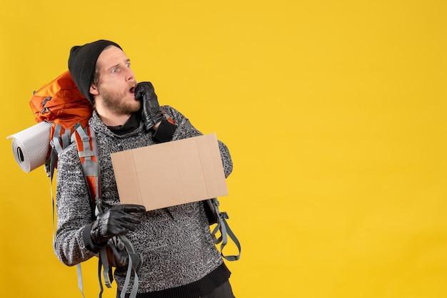 Vorderansicht des erstaunten männlichen anhängers mit lederhandschuhen und rucksack, der leeren karton hält