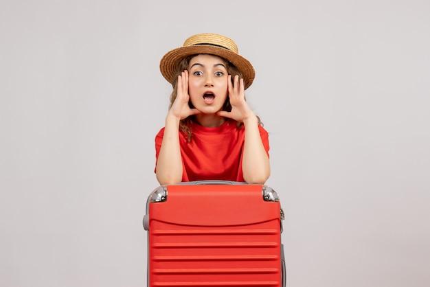 Vorderansicht des feiertagsmädchens mit ihrem koffer, der jemanden anruft, der auf weißer wand steht