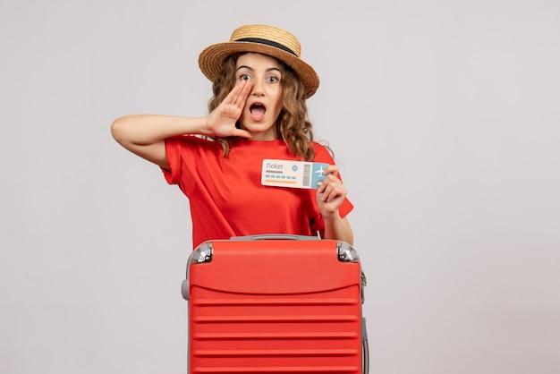 Vorderansicht des ferienmädchens mit ihrem valise, der ticket anruft, das jemanden anruft