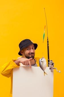 Vorderansicht des fischers angelrute halten und auf leeres plakat zeigend