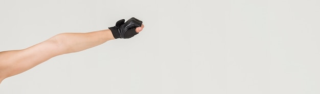 Vorderansicht des frauenarms, der einen turnhandschuh trägt