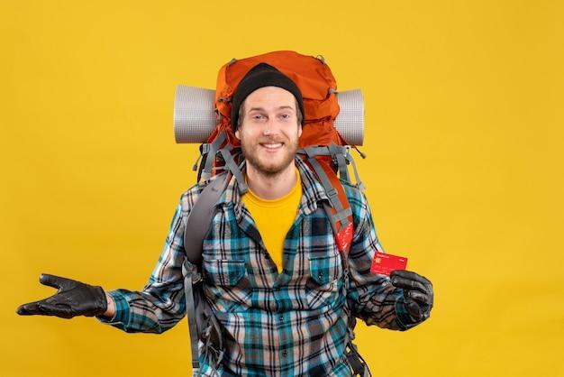 Vorderansicht des freudigen jungen rucksacktouristen mit dem schwarzen hut, der kreditkarte hält