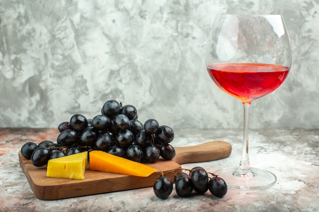 Vorderansicht des frischen köstlichen schwarzen traubenbündels und des käses auf dem hölzernen schneidebrett und einem glas wein auf gemischtem farbhintergrund