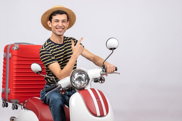 Vorderansicht des fröhlichen jungen mannes mit strohhut auf moped, der auf etwas zeigt