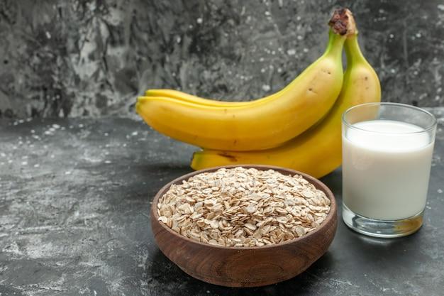 Vorderansicht des frühstückshintergrundes mit bio-haferkleie in einer braunen holztopfmilch in einem glasbananenbündel auf dunklem hintergrund
