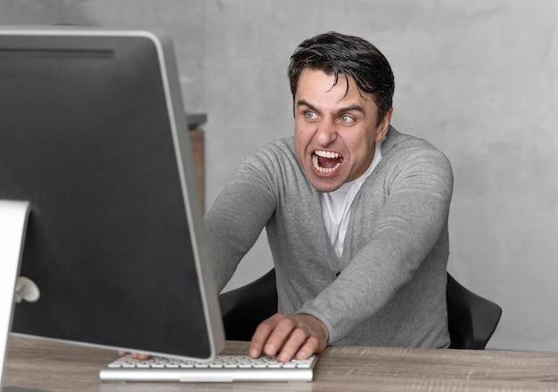 Vorderansicht des frustrierten mannes, der im medienfeld mit computer arbeitet