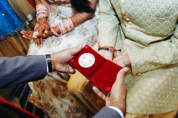 Vorderansicht des gebens von geschenken auf traditioneller indischer hochzeitszeremonie