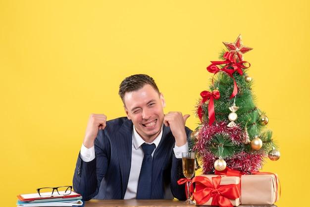 Vorderansicht des gelächelten mannes, der auf weihnachtsbaum zeigt, der am tisch nahe weihnachtsbaum und geschenke auf gelb sitzt