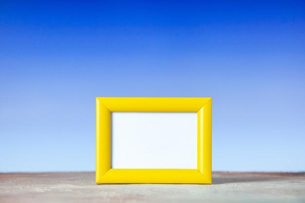 Vorderansicht des gelben leeren bilderrahmens, der auf dem tisch auf weißer und blauer oberfläche mit freiem platz steht