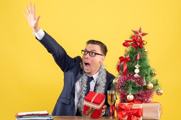 Vorderansicht des gerufenen mannes, der jemanden anruft, der am tisch nahe weihnachtsbaum sitzt und auf gelb präsentiert. Kostenlose Fotos