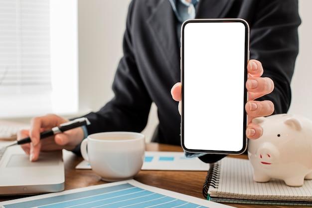 Vorderansicht des geschäftsmannes am büro, das leeres smartphone hält