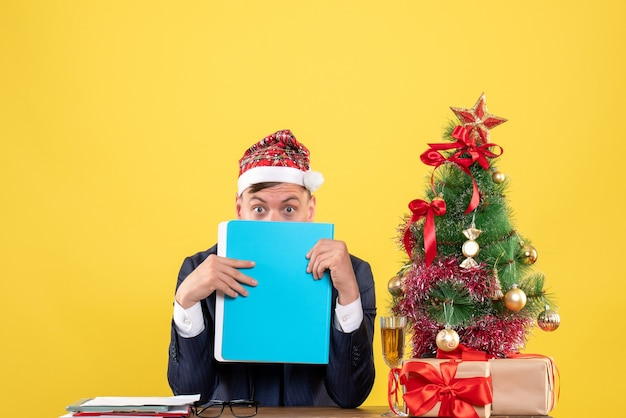 Vorderansicht des geschäftsmannes bedecken sein gesicht mit aktenordner, der am tisch nahe weihnachtsbaum sitzt und auf gelber wand präsentiert