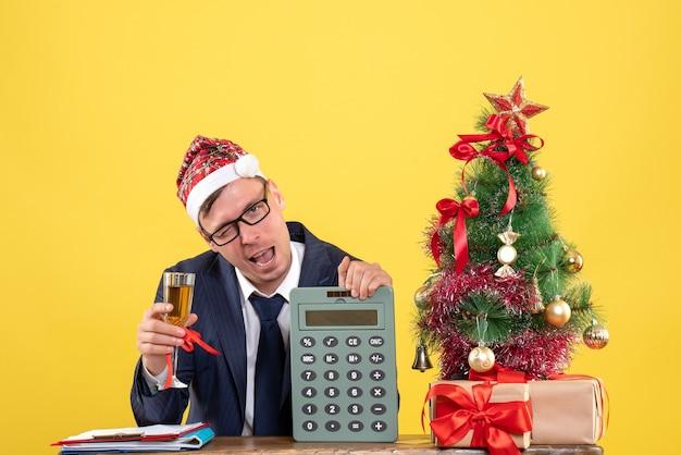 Vorderansicht des geschäftsmannes, der anstößt, der am tisch nahe weihnachtsbaum sitzt und auf gelb präsentiert