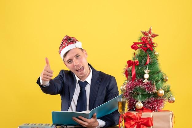 Vorderansicht des geschäftsmannes, der daumen hoch zeichen macht, das am tisch nahe weihnachtsbaum und geschenken auf gelb sitzt
