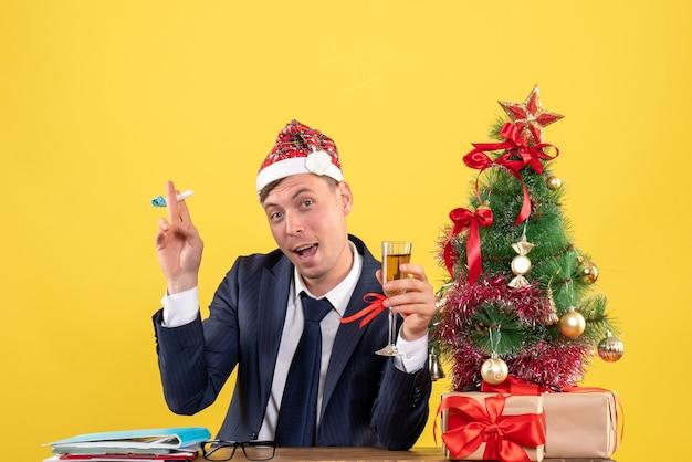 Vorderansicht des geschäftsmannes, der den krachmacher anstößt, der am tisch nahe dem weihnachtsbaum sitzt und auf gelb präsentiert