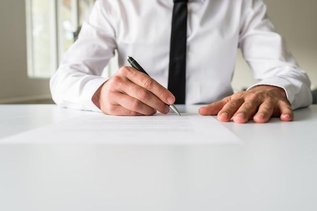 Vorderansicht des geschäftsmannes, der ein dokument unterzeichnet