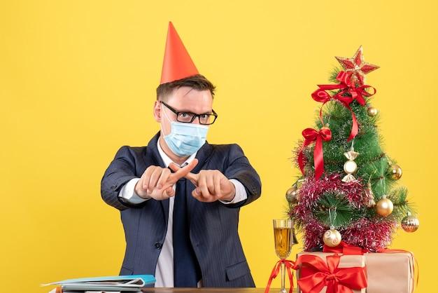 Vorderansicht des geschäftsmannes, der finger kreuzt, die am tisch nahe weihnachtsbaum sitzen und auf gelber wand präsentieren