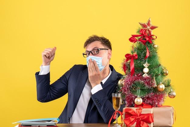 Vorderansicht des geschäftsmannes, der hand auf seinen mund setzt, der am tisch nahe weihnachtsbaum sitzt und auf gelb präsentiert