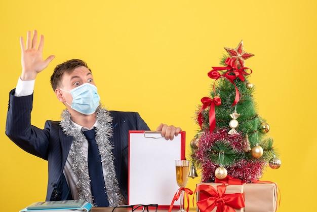 Vorderansicht des geschäftsmannes, der jemanden begrüßt, der am tisch nahe weihnachtsbaum sitzt und auf gelb präsentiert.