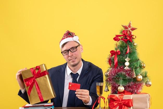 Vorderansicht des geschäftsmannes, der karte und weihnachtsgeschenk hält, sitzt am tisch nahe weihnachtsbaum und präsentiert auf gelb.