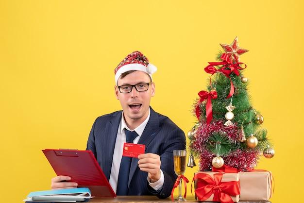 Vorderansicht des geschäftsmannes, der karte zeigt, die am tisch nahe weihnachtsbaum sitzt und auf gelb präsentiert