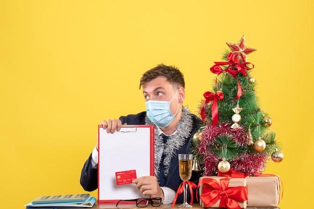 Vorderansicht des geschäftsmannes, der klemmbrett und kreditkarte hält, die am tisch nahe weihnachtsbaum und geschenken auf gelb sitzen