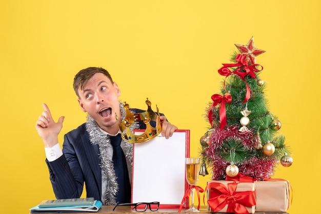 Vorderansicht des geschäftsmannes, der klemmbrett und krone hält, sitzt am tisch nahe weihnachtsbaum und präsentiert auf gelb