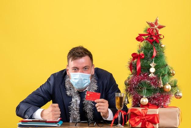 Vorderansicht des geschäftsmannes, der kreditkarte hält, die am tisch nahe weihnachtsbaum und geschenken auf gelb sitzt