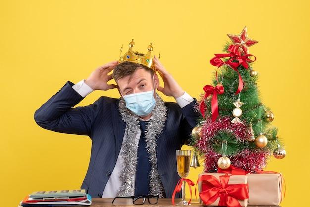 Vorderansicht des geschäftsmannes, der krone hält, die am tisch nahe weihnachtsbaum sitzt und auf gelb präsentiert