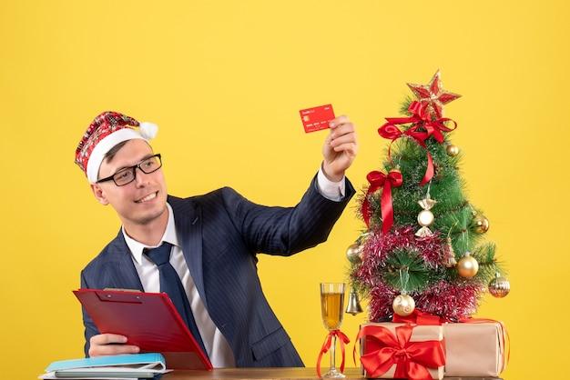 Vorderansicht des geschäftsmannes, der seine karte betrachtet, die am tisch nahe weihnachtsbaum sitzt und auf gelb präsentiert
