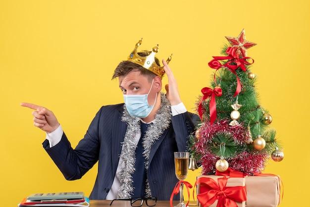 Vorderansicht des geschäftsmannes, der seine krone hält, die am tisch nahe weihnachtsbaum sitzt und auf gelb präsentiert