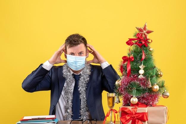 Vorderansicht des geschäftsmannes, der seine maske abnimmt, die am tisch nahe weihnachtsbaum sitzt und auf gelb präsentiert.