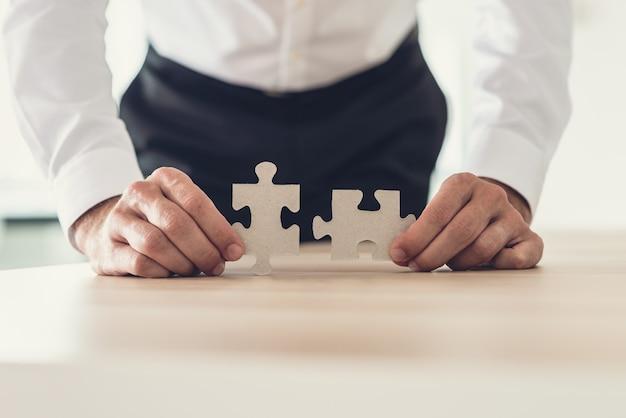 Vorderansicht des geschäftsmannes, der zwei passende puzzleteile hält, die auf seinem schreibtisch gelehnt sind.