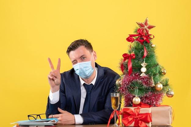Vorderansicht des geschäftsmannes mit dem blinkenden auge, das siegeszeichen macht, das am tisch nahe weihnachtsbaum und geschenken auf gelb sitzt