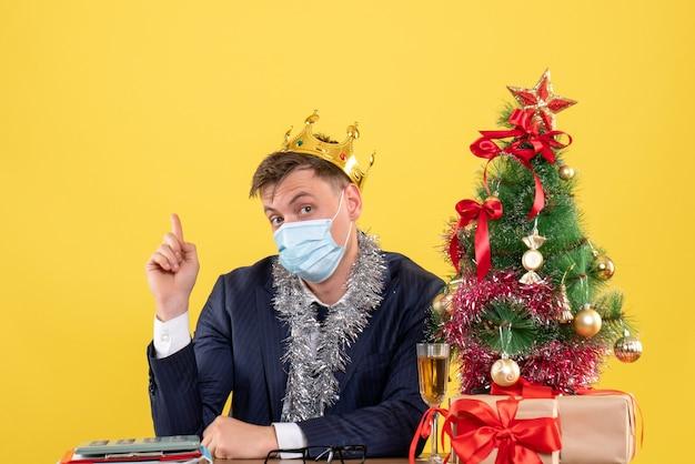 Vorderansicht des geschäftsmannes mit krone, die am tisch nahe weihnachtsbaum sitzt und auf gelb präsentiert