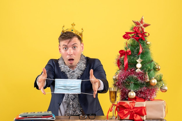Vorderansicht des geschäftsmannes mit krone, die maske hält, die am tisch nahe weihnachtsbaum und geschenken auf gelb sitzt