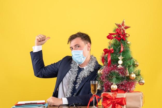 Vorderansicht des geschäftsmannes mit maske, die am tisch nahe weihnachtsbaum sitzt und auf gelb präsentiert